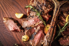 Appetizer board serving of grilled and slice porterhouse steak with fresh herbs,garlic and a white horseradish sauce.