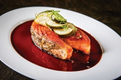Bone-In Salmon Steak with Teriyaki Glaze topped with Asian Pickles served on a white oval plate on a wood surface.