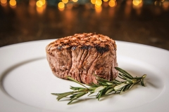 grilled 8 ounce tenderloin steak served on a white plate with a sprig of fresh rosemary on a brown wood table surface.