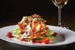 Sliced wedge of iceberg lettuce with bacon, Tomato, Onion, Scallion, French and Blue Cheese Dressing served with a glass of white wine on a dark wood table.